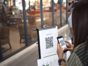people scan qr code for check in on supermarket or tacking time line, coronavirus or covid 19, new normal